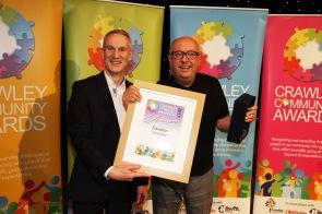 DM17311565a.jpg. Crawley Community Awards, 2017. David Reid receives the Education award from Mark Haynes. Photo by Derek Martin